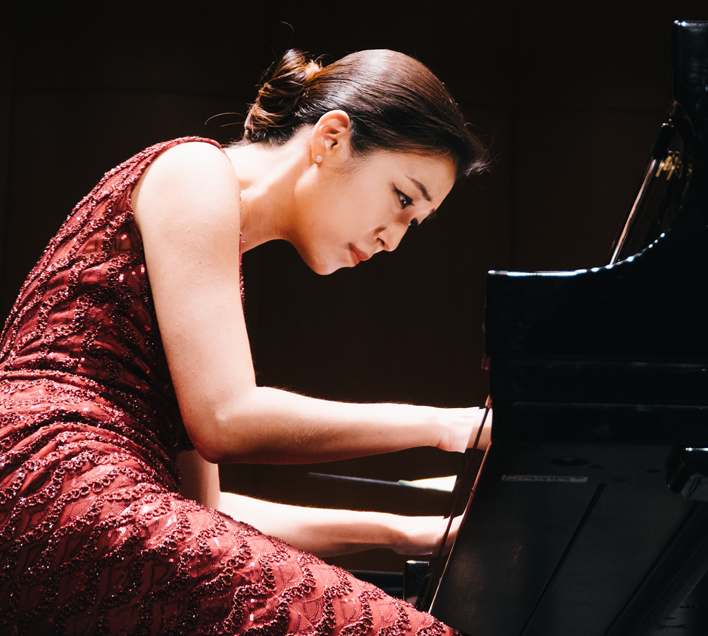 Pianist on stage in concert attire, playing at Bovard Auditorium.