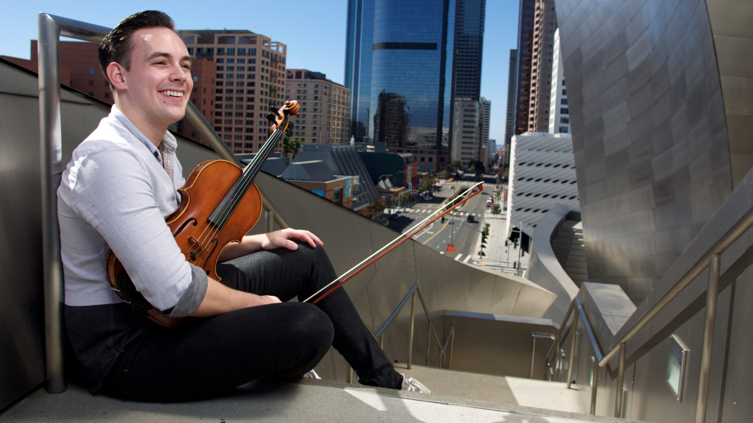 Student violinist holding their instrument smiles outside Walt Disney Concert Hall in Downtown Los Angeles.